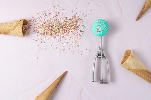 Colher com um sorvete smurf e alguns cones de wafer e cobertura em um fundo rosa. vista do topo. copie o espaço.