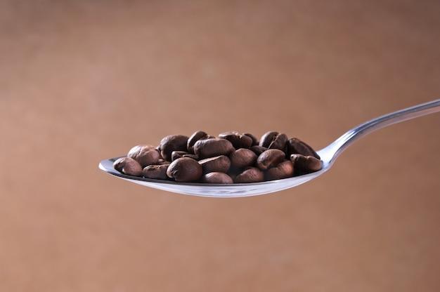 Colher de aço de grãos de café torrados no fundo marrom claro close-up