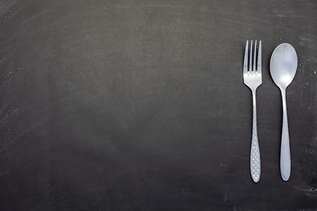 Colher de aço inoxidável e garfo em madeira preta ou fundo de lousa com copyspace