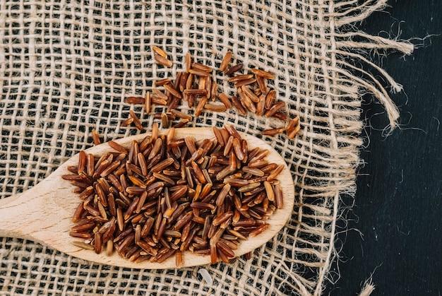 Colher de arroz vermelho em pano de linho
