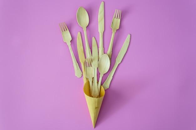 Colher de bambu e garfo em uma linha no fundo rosa ou violeta