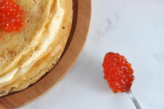 Colher de chá com caviar vermelho e panquecas.