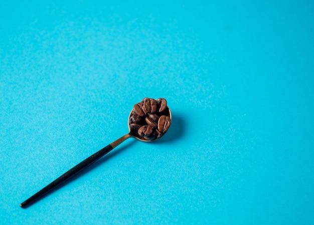 Colher de chá com grãos de café em uma parede azul