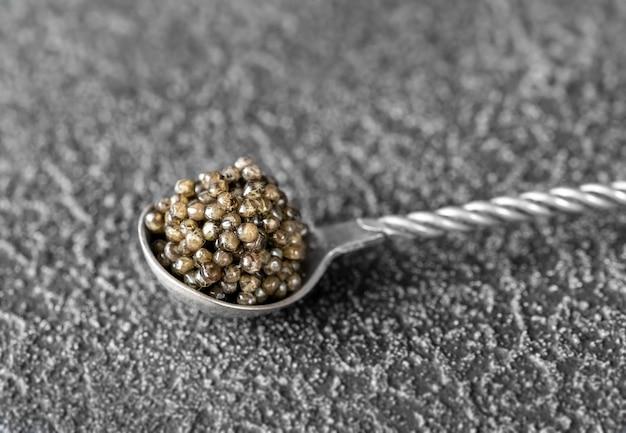 Colher de chá de prata de caviar preto de perto