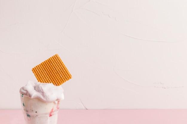 Colher de gelo cremoso com palha de waffle em tigela de plástico