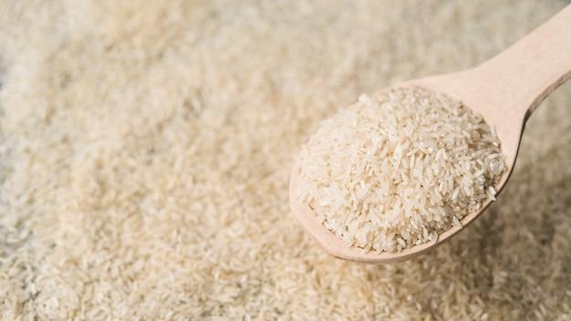 Colher de madeira cheia de arroz cru sobre o cenário de arroz embaçada