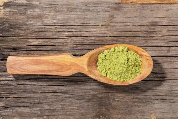 Colher de madeira com pó verde do chá do matcha na madeira. vista do topo.