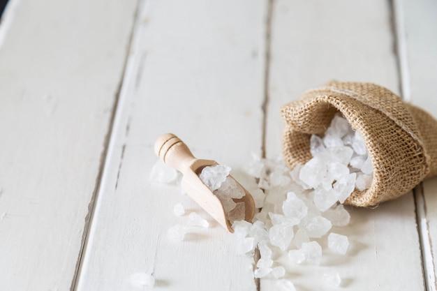 Colher de madeira de açúcar cristalino e saco de açúcar no chão de madeira branco