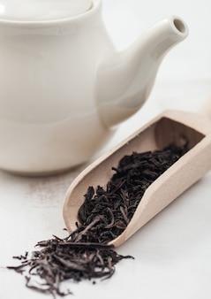 Colher de madeira de chá preto solto com bule de cerâmica branca sobre fundo branco.