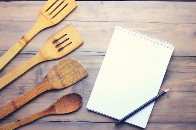 Colher de madeira de cozinha, papel e pancil na mesa de madeira