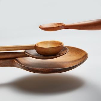 Colher de madeira diferente isolada no ar em um fundo branco