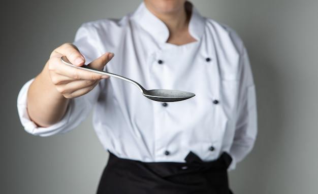 Colher de mão de chef cozinhar preparar comida no restaurante de cozinha quero que você tenha um sabor delicioso