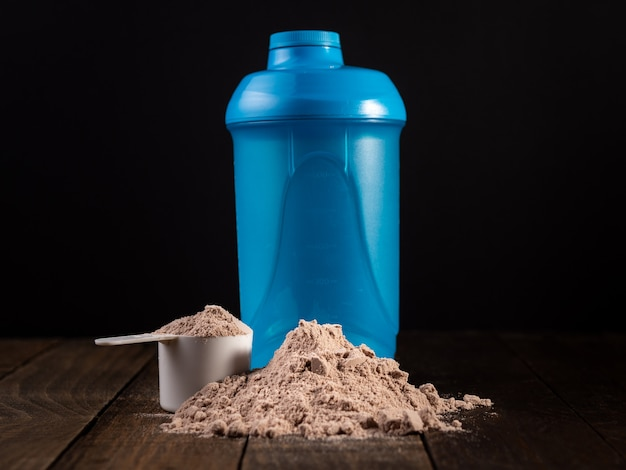 Colher de medição de proteína de soro de leite na mesa de madeira para preparar um milk-shake.
