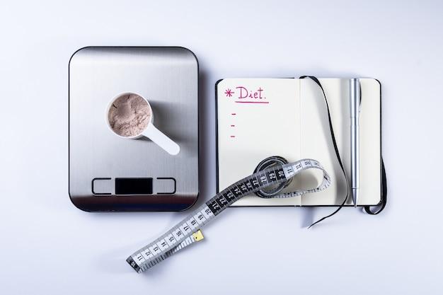 Colher de medição de proteína de soro de leite, notebook, balança e fita métrica para dieta.