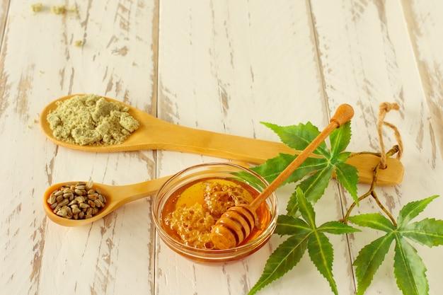 Colher de mel com folhas de cannabis, mel de cânhamo cbd, sementes e pó. ingredientes da medicina alternativa na mesa de madeira.