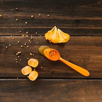 Colher de mel perto de pétalas de flores e doces em fundo de madeira