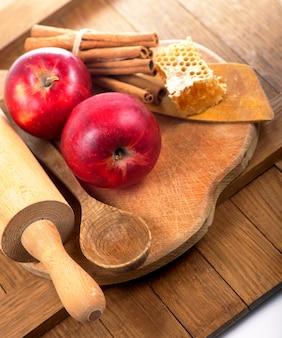 Colher de mel, pote de mel, maçãs e canela em um fundo de madeira em estilo rústico.