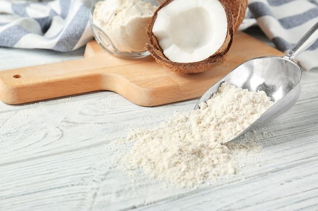 Colher de metal com farinha de coco na mesa de madeira