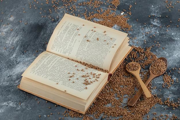 Colher de pau cheia de trigo sarraceno cru e livro na superfície de mármore