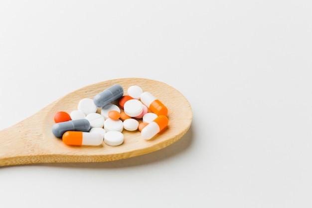 Colher de pau cheio de comprimidos
