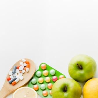 Colher de pau cheio de pílulas e maçãs
