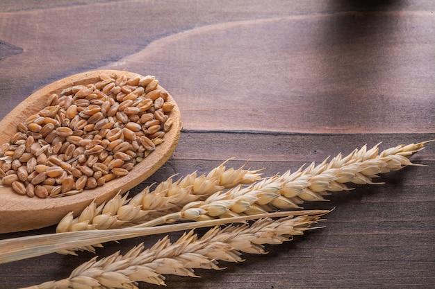 Colher de pau com calos e espigas de trigo na placa vintage