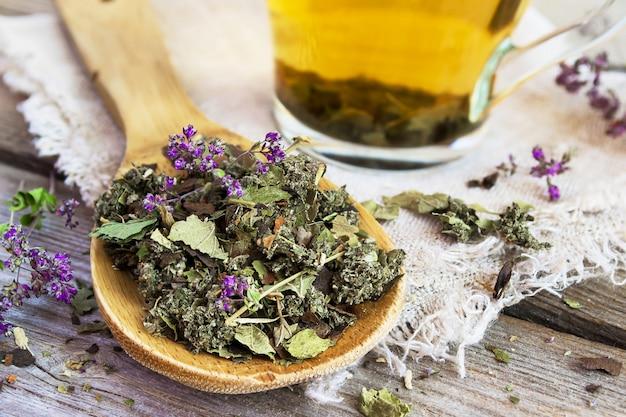 Colher de pau com chá de ervas seca.
