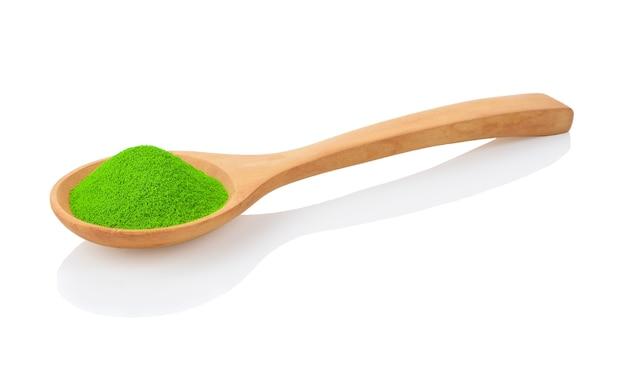 Colher de pau com chá verde matcha em pó, isolado no branco