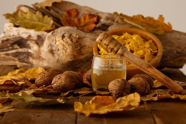 Colher de pau com mel escorrendo em uma jarra, nozes e cereais na parede embaçada de folhas de outono