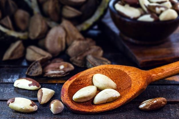 Colher de pau com muitas castanhas do brasil, nós amazônicas usadas na culinária mundial