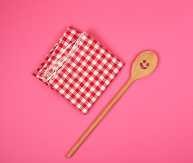 Colher de pau com um rosto esculpido em uma toalha de cozinha vermelha