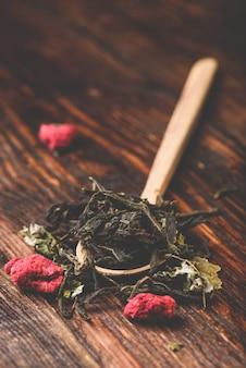 Colher de pau de chá de ervas de framboesa sobre a mesa de madeira