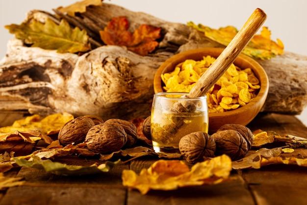 Colher de pau dentro de um pote de mel com nozes e uma tigela de cereal no outono folhas fundo desfocado
