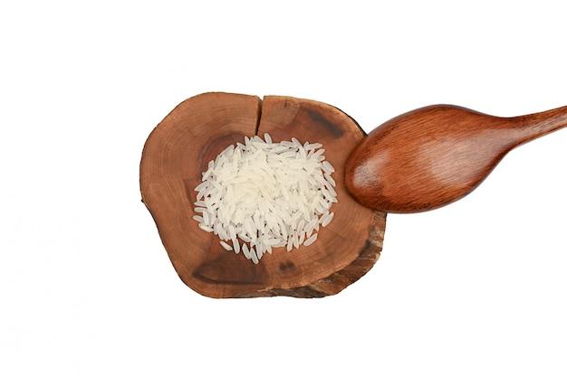 Colher de pau e arroz branco em uma placa de madeira