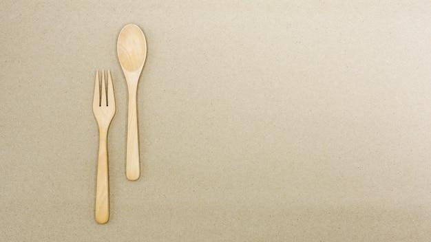 Colher de pau e garfo em papel pardo - fundo
