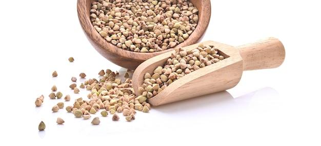 Colher de pau e tigela de fundo de groat de trigo sarraceno torrado, grão antigo sem glúten para dieta saudável, foco seletivo