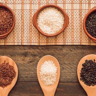 Colher de pau e tigela de grãos de arroz na mesa de madeira