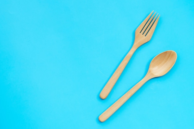 Colher de pau e um garfo sobre fundo azul.