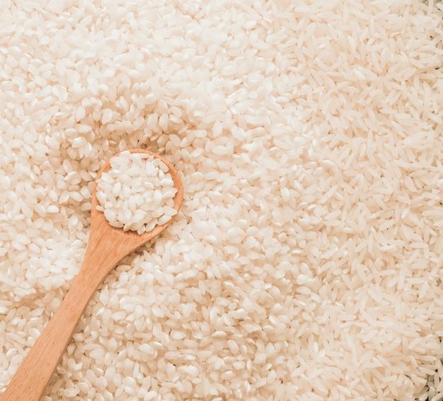 Colher de pau em grãos de arroz branco cru