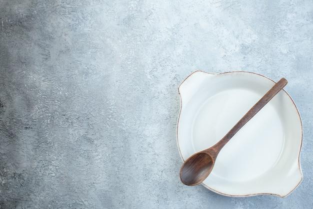 Colher de pau em prato de sopa branco vazio na metade da superfície cinza claro