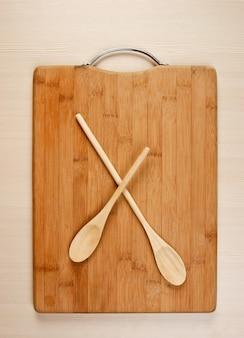 Colher de pau na tábua de bambu da cozinha