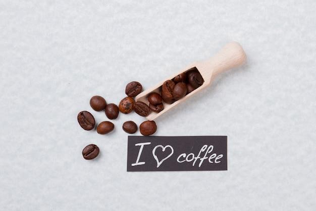 Colher de pau ou colher e grãos de café. eu amo o conceito de café. isolado na superfície branca