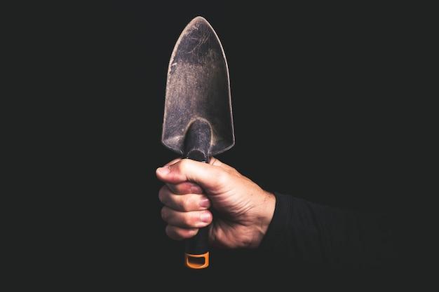 Colher de pedreiro para jardinagem em uma mão de homem, serviço de manutenção