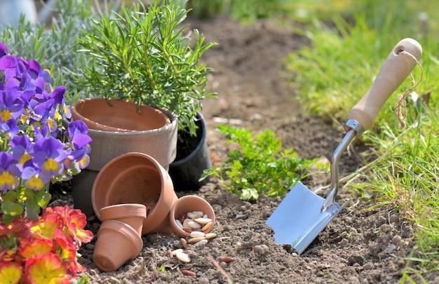 Colher de pedreiro plantar na terra ao lado de vasos de flores em um jardim