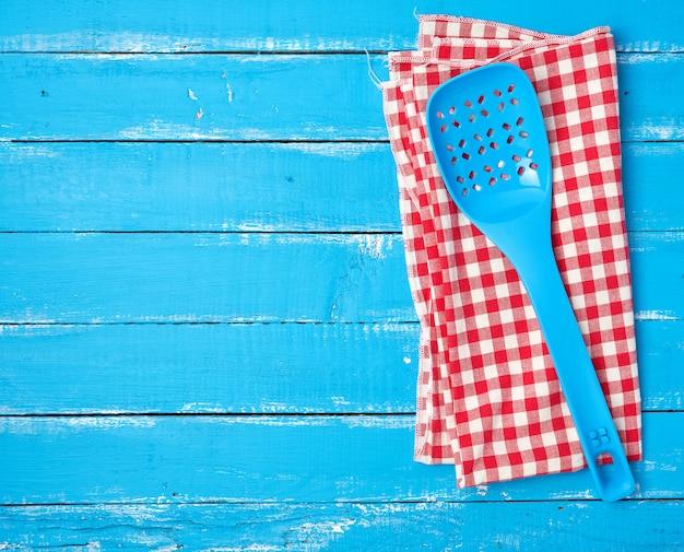 Colher de plástico azul com buracos em um guardanapo de têxteis vermelho