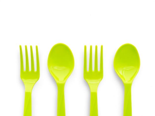 Colher de plástico verde e garfo isolado no branco