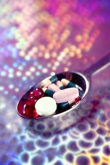 Colher de prata cheia de comprimidos de medicamento sobre holográfico