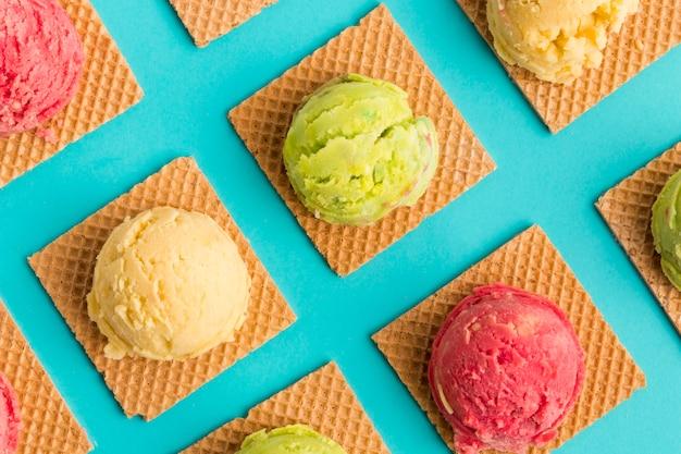 Colher de sorvete de frutas em waffles quadrados na superfície turquesa