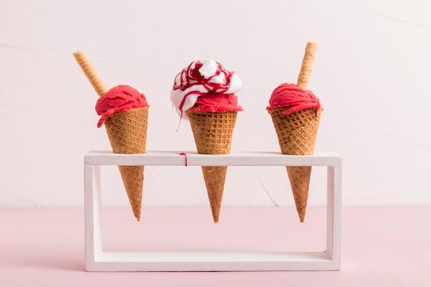 Colher de sorvete vermelho em cones com xarope e palha de waffle em stand