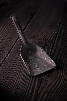 Colher do ferro em uma tabela de madeira, vila material natural.